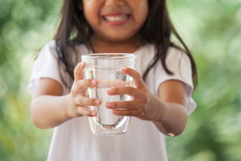 Little girl holding glass of fresh water